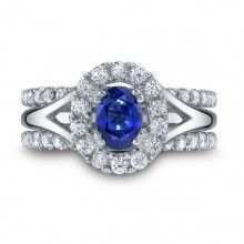 Kirk Kara Sapphire Halo Engagement Ring from the Carmella Collection In 18kt White Gold Featuring 0.40 Carats Round Cut Diamonds And 1 Carat Oval Sapphire Center Gemstone. Price Includes Center Sapphire.