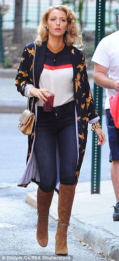 Pretty: The 28-year-old wore a bird-print jacket over a clashing blouse, but still looked stunning in it, as she pounded the streets with a juice in hand
