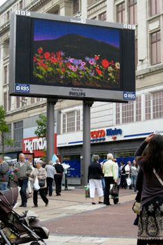 On Liverpools Claytons Square, anyone with a blue tooth device contributed a virtual flower onto the screen. If two people approached each other to talk, their towers grew bigger.