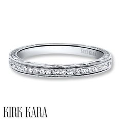 This elegant wedding band from the Kirk Kara collection showcases sparkling round diamonds accented above and below by double rows of milgrain detail. Crafted of 18K white gold, the ring has a total diamond weight of 1/5 carat. Diamond Total Carat Weight may range from .18 - .22 carats.