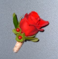 Red rose boutonniere with hypericum berry accent and stem wrapped in ribbon