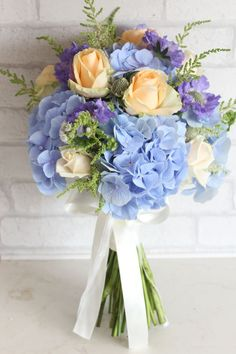 Light blue hydrangea and peach roses wedding bouquet. 4 Seasons Flowers