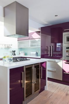 This purple kitchen sings!  The sleek contemporary cabinets couples with the white creates a space that is dynamic and fun!
