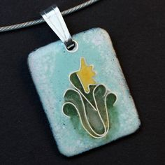 Very pretty enamel pendant done in the cloisonne style. Shades of blue are fired on a copper base. Fine silver wires are shaped into an abstract flower design and enameled in green and yellow