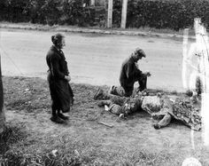 French civilians placing flowers on a dead American soldier,after the Battle of Carentan, Normandy, June 1944