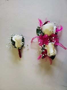 White roses, baby's breath, green leaves, pink bow with pink feathers on a wristlet and matching boutonniere. Corsage And Boutonniere, Boutonnieres, Pink Feathers, Wrist Corsage, Baby's Breath, Corsages, White Roses, Green Leaves, Bows