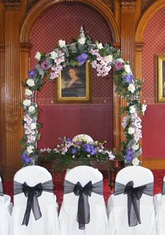 The luxurious bridal arch in place for the wedding ceremony in The Grand Ballroom, Haigh Hall.  Dressed in purples, lilacs and ivorys.  The white chair covers contrasted with a black sash.  www.am-flowers.co.uk