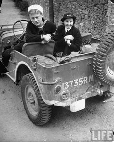 A US Navy yeoman and a member of the Women's Royal Naval Service (WRENS) sitting in a US Jeep marked with a Royal Navy license at the US Naval Operations Base. Londonderry, United Kingdom, 1942 ~