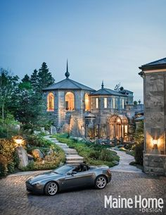 "This view is coming down the cobblestone driveway. The Front entry can be seen with the glassed archway & bridge. The stone facade was to replicate the home ""growing"" up out of the beautiful ledge it sits on. The unique shape of the home is dedicated to the set back's and property lines."