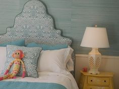 pretty grass cloth wall covering and lovely custom upholstered headboard.  soft blues and whites