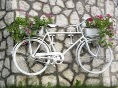 Why not spray paint your old bike and place on your wall with a some beautiful colourful planters at either side.