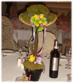 Topiary with hat of moss and flowers