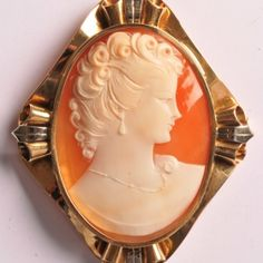 Art Deco shell cameo brooch of a woman in profile to the right, white on orange background.  Set in an engraved 18 carat white and yellow gold frame.  50 x 58mm  www.Osprey.fr   €1240 Orange Background, Shells, Vintage Jewelry, Profile, Paris, Jewels, Woman, Deco, Yellow