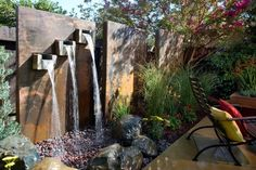 This unique three-tiered waterfall with stone trough is faced with rustic steel panels that add privacy and provide an impressive visual backdrop to a new patio seating area.