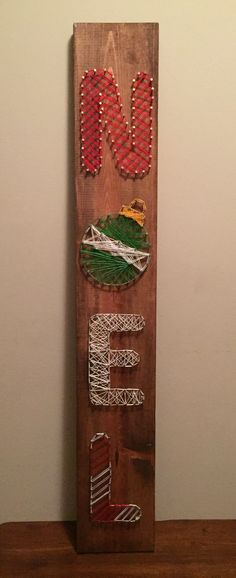 Noel sign made with string art on wood plank