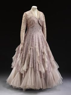 1948 [Dress] Evening dress of lilac tulle with an embroidered vermicular pattern, which is re-embroidered in flower shaped sequins in shades of mauve and lilac. The skirt border and the lobed scalloped panels applied to it are trimmed with grey tulle.
