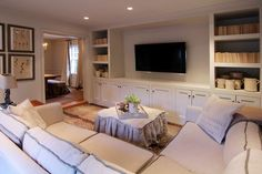 The step-down family room features dramatic Stark Antelope carpet and a wall of bookcases with a central television shelf or flat-screen television mount.