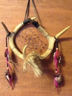 This dream catcher is made with 2 deer antlers has black artificial sinew webbing with tigers eye and rhodonite gemstones in the web has brown sheepskin hanger at the top has coyote fur attached at the bottom Has natural and dyed rooster feathers attached with glass beads on the strands of sheepskin on each side   measures 11 inches wide and total length is 18 inches has a total of 5 points