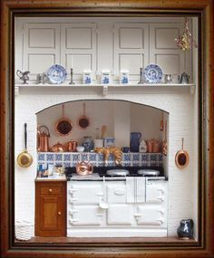 Miniature dollhouse kitchen with an Aga stove and rack full of blue porcelain dishware