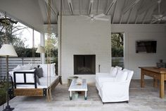 Heather A Wilson, Architect: Covered patio with white brick fireplace, hanging rattan swing sofa, pair of white ...