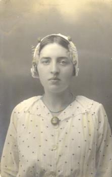 Portretfoto (ingekleurd) van een onbekende vrouw vermoedelijk behorende tot de familie Van den Band verkleed in Vlaardingse klederdracht, gedateerd augustus 1915