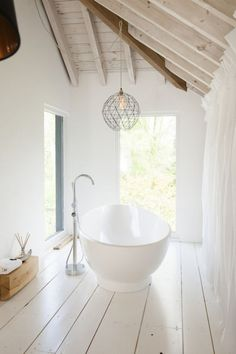 Un coin salle de bain aménagé sous les toits, avec un parquet rustique repeint en blanc, très joli.