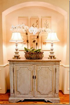 Love orchids. This has such a warm, cozy feel to it.  Repaint my foyer buffet?