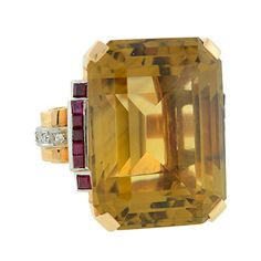 Straight from the Retro era (ca1940), this enormous faceted citrine is framed by luscious rubies and sparkling diamonds in a 14kt gold setting.