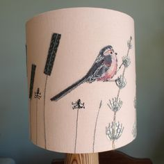 Long tailed tit lampshade. This lampshade, part of my Garden Birds Collection features a long tailed tit on a pink background. I have made this lampshade using appliqué, free-motion embroidery and hand-dyed fabrics and wools. It produces a lovely glow when illuminated.This item is handmade and therefore one-of-a-kind.