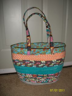 Coiled basket swimming bag. This is made using stripe of material sewed around a clothesline and then zigzagged together to make a basket. I also sewed material around some handles.