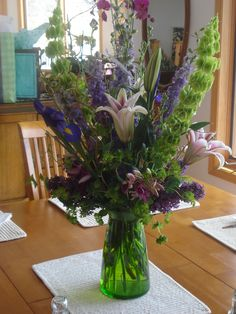 Kitchen centerpiece with bells of ireland and larkspur by Petals.