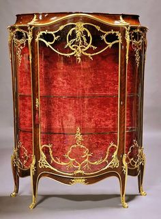 """A Fine French 19th/20th Century Louis XV Style Kingwood and Ormolu Mounted Single-Door Vitrine, the demi-lune shaped cabinet with and arched bonnet, molded trim above a bombé glazed door framed with rocaille within a """"C"""" scroll and stylized acanthus cast encadrements issuing shaped circular foliate and budding branch reticulated bronzes over similary molded pierced """"C"""" scrolled and blossoming stem mounts cornered by berried laurel interwined with lattice form details flanked by corners of…"""