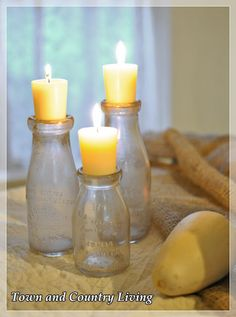Old milk bottles with votives tucked into the top - Town & Country Living