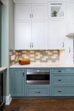 Modern coastal craftsman kitchen with bright blue cabinetry, dark wood floors, and grey subway tile backsplash.