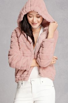 A soft faux fur jacket featuring a ribbed pattern, hoodie, a zippered front, an elasticized hem, front slip pockets, and long sleeves. This is an independent brand and not a Forever 21 branded item.