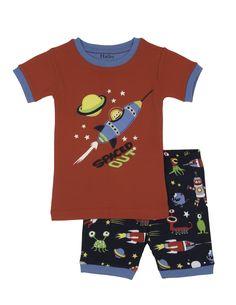 Jongens pyjama Space Alien van het kinderkleding merk Hatley  Dit is een rode jongens kinderpyjama uit 2 delen. Een rode pyjama tshirt met een korte mouw, afgewerkt met licht blauw. De shirt heeft een grote mooie tekening van een spaceshuttle in de ruimte. Met tekst : Spaced out Een donker blauwe korte pyjama broek met een all over print.