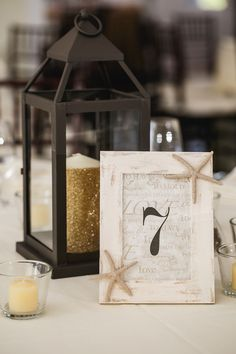 Votive candles, lanterns, gold glitter candles & a lovely wooden starfish frame for table numbers! {@susieandbecky}