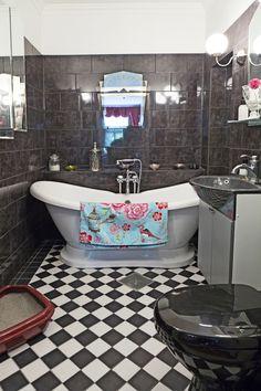Mustavalkoinen art deco -kylpyhuone, jossa on komea amme. Black and white art deco bathroom with tube. | Puuhelle vaaleassa keittiössä. Stove in a light kitchen. | Unelmien Talo&Koti Toimittaja: Anette Nässling Kuva: Toni Härkönen