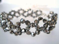 """Armbåndet er """"vevd"""" sammen av sølvsorte Swarovski krystaller( 4 mm store hver) tredd på wire i stål. Krystallene er lett foliert på den ene siden og med en mørk sølvaktig glans gjennom dem. Krystal"""