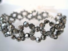 """Armbåndet er """"vevd"""" sammen av sølvsorte Swarovski krystaller( 4 mm store hver) tredd på wire i stål. Krystallene er lett foliert på den ene siden og med en mørk sølvaktig glans gjennom dem."""