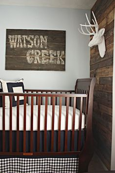 Reclaimed lumber (pallet) wall and faux taxidermy create a wonderful and unique nursery theme.