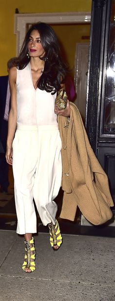 Amal Clooney Ditched Her Dress For Date Night, choosing a sleek white, oversize jumpsuit, yellow strappy heels, and metallic accessories.