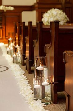 Floating Votive Candles In Varying Sizes Cast A Soft Glow Over This Wedding Aisle
