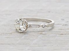 Engagement ring made in platinum and centered with a GIA certified 1.03 carat old European cut diamond with J color and VS1 clarity. Accented with wheat pattern engraving and .50 carats of baguette an