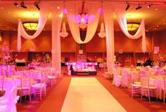White swag hanging from the ceiling with pink lighting. Formal events.