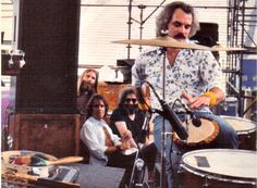 Bill Kreutzmann, playing a djembe during a concert in Denver. Grateful Dead band members Brent Mydland, Bob Weir and Jerry Garcia (from left to right) are in the background.