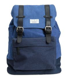 Blue. Backpack in canvas with imitation leather details. Handle at top and opening with drawstring, flap, and metal fastener. Lightly padded backplate and