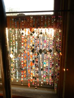 Sun catcher beaded curtain - memories of the bead and mirror curtain in my mums summer house/ garden shed - made with her hand made beads and little mirror tiles strung on fishing line.