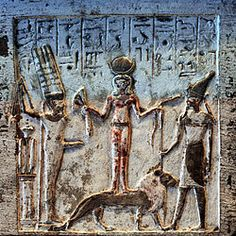 In the Qetesh stele, she is represented as a frontal nude standing on a lion between Min of Egypt and the Canaanite warrior god Resheph. She is holding snakes in one hand and a lotus flower in the other as symbols of creation. She is associated with Anat, Astarte, and Asherah. She also has elements associated with the goddesses of Myceneae, the Minoans of Crete, and certain Kassite goddesses of the metals trade in Tin, Copper and Bronze between Lothal and Dilmun.