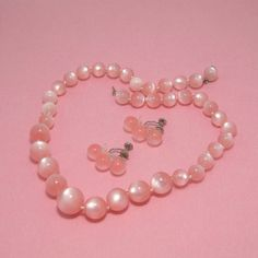 Candy floss pink is the color of these lucite beads! Graduated in size, the beads (hand knotted between each one) form a necklace that is beautifully feminine, very vintage. Matching earrings are three beads in a slightly curved linear arrangement, on silver tone screw backs. So pretty and subtle.